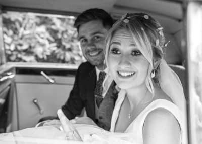 bride and groom happy in wedding car