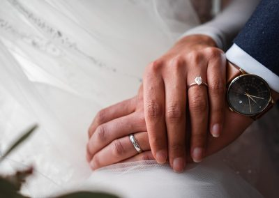 Bride-and-groom-holding-hands-with-rings