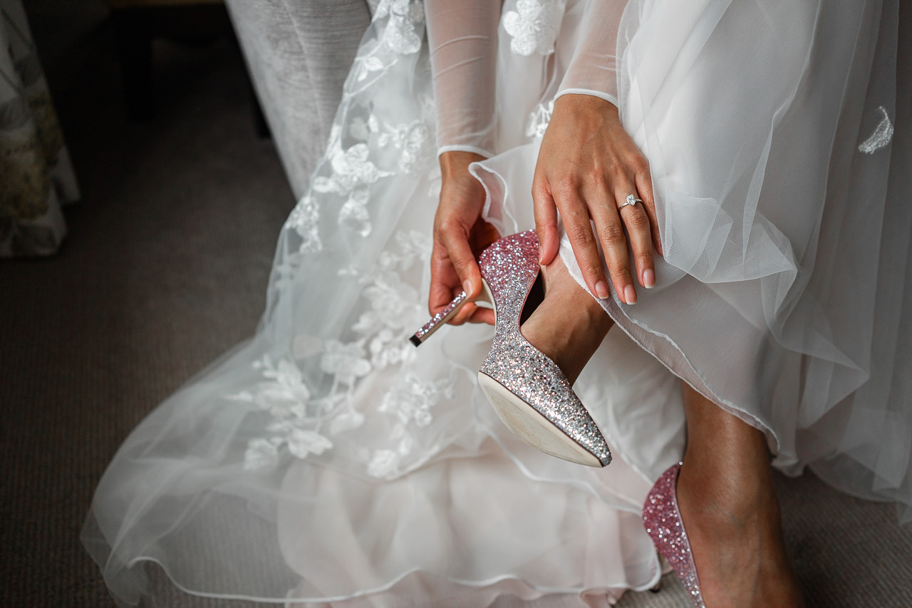 Bride putting on glittery shoes