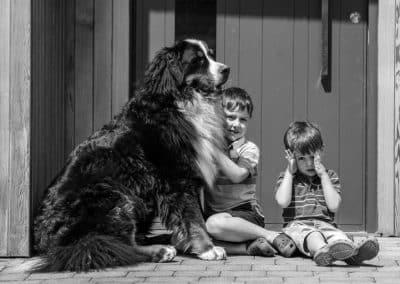 big-dog-sitting-with-children-black-and-white-photo-in-hertfordshire