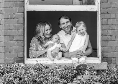 black-and-white-photo-family-looking-through-window-frame