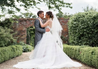 bride-and-groom-holding-each-other-in-walled-garden