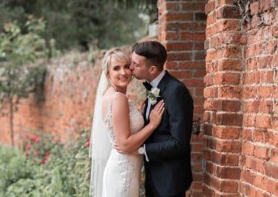 bride-groom-kinssing-by-walled-garden