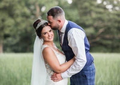 groom-kissing-bride-in-green-field