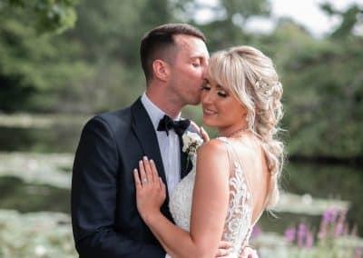 groom-kissing-side-of-bride-by-lake