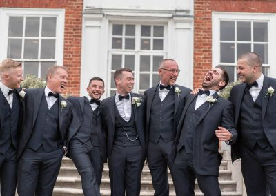 groom-and-bestman-laughing-together-at-stoke-place