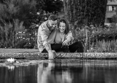 black-and-white-photo-engaged-couple-sitting-by-pond-at-the-grove-hotel