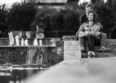 black-and-white-photo-engaged-couple-sitting -by-waterfall-the-grove-hertfordshire