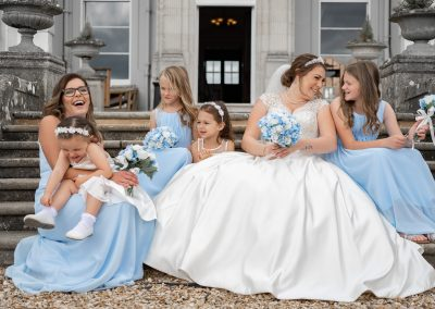 bride-and-bridesmaids-in-blue-sitting-on-steps-at-wokefield-estate
