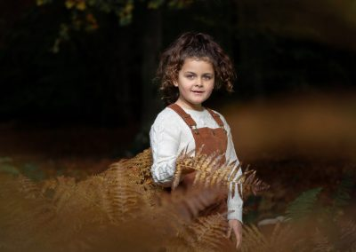 child-portrait-in-tan-dress-in-autumn-leaves