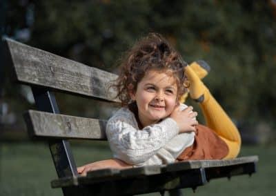 child-portrait-park-bench-in-autumn-leaves