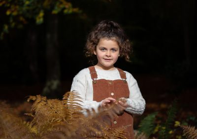 child-standing-in-brown-ferns-in-autumn-leaves