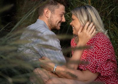 couple-engaged-in-tender-hold-together-amongest-tall-grass