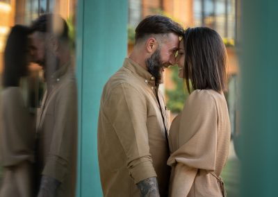 engaged-couple-facing-each-other-and-embracing-in-the-gardens-at-the-grove-hotel-hertfordshire