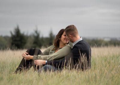 engaged-couple-sitting-in-grass-field-the-grove-hotel-hertfordshire