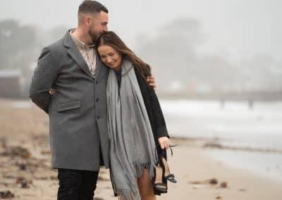 engaged-couple-walking-on-swanage-beach