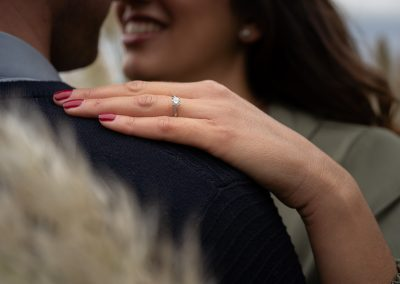 engagement-ring-on bride-to-be-on-groom-shoulder-at-the-grove-hertfordshire