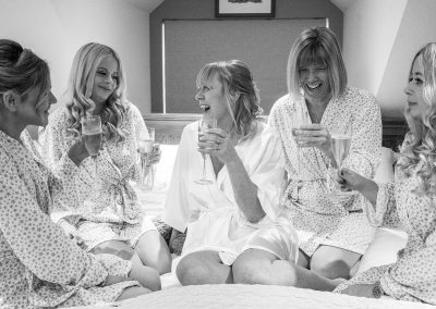 bride-and-brides-maids-sitting-on-bed-black-and-white-photo