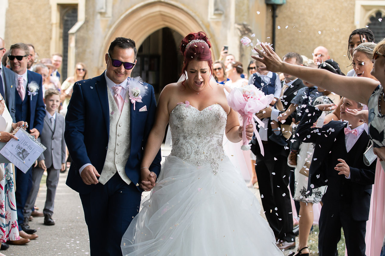 groom-and-bride-walking-through-confetti-at-the-church