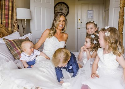 bride-sitting-on-bed-with-pageboys-and-flower-girls