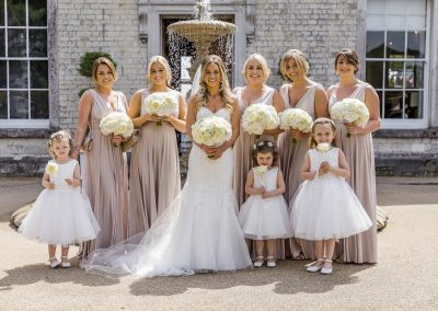 bride-standing-with-bridesmaids-and-page-boy-outstanding-froyle-park
